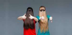 Two women showing thumbs up and thumbs down wearing sunglasses, their faces hidden by their hair
