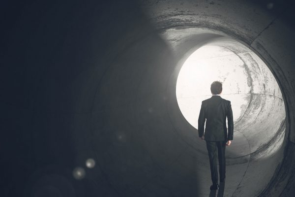 Man in a suit looking at the light at the end of a tunnel