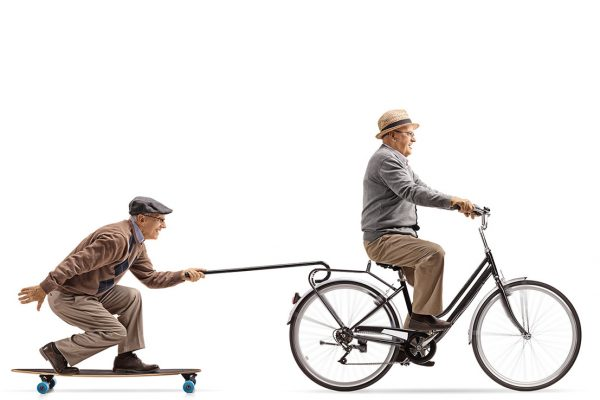 Senior on a skateboard being towed by another senior on a bike.