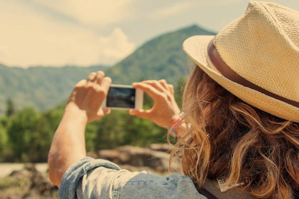 Woman taking photo of mountains with a phone.